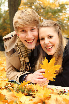 Young Couple with autumn leaves. Happy teens in love