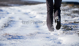 The legs of a hiker walking through a snow covered winter landscape. Edmondbyer Common, England, UK.