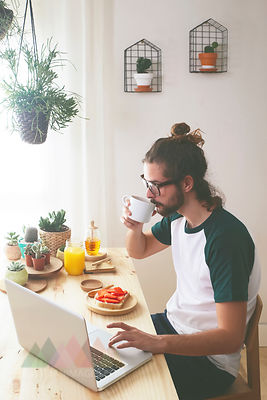 Young man using laptop while having breakfast