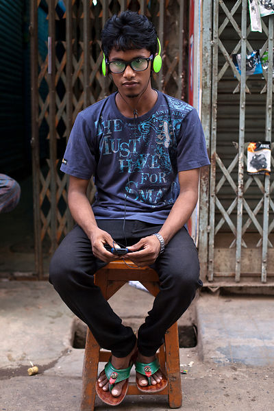 Bangladesh - Dhaka - A fashionably dressed young man listens to music on the mobile phone with headphones