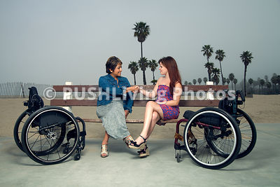 Two women in wheelchairs at a beachside park
