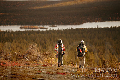 Hikers above forest and lake