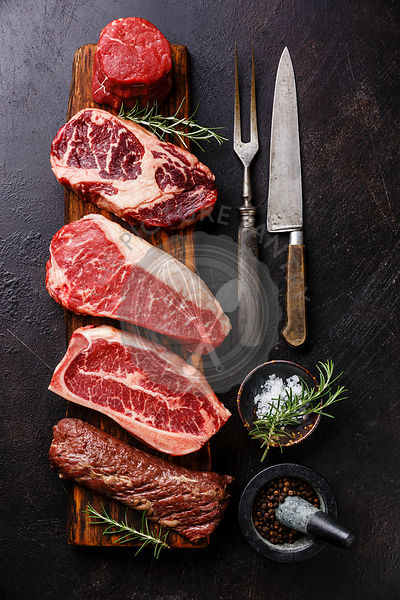 Variety of Raw Black Angus Prime meat steaks Tenderloin fillet mignon, Rib eye, Striploin, Blade, Machete on wooden board and seasoning