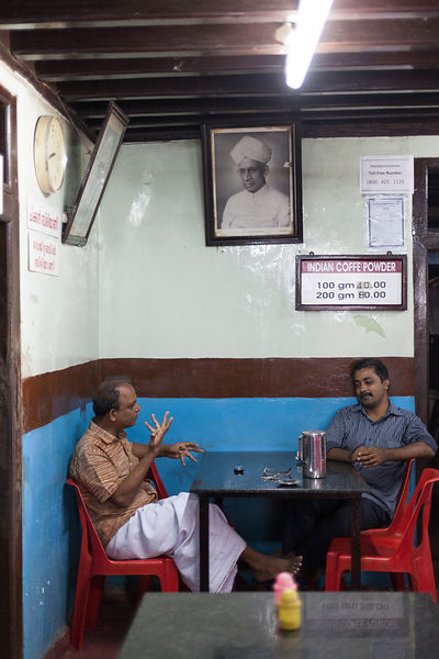 India - Alappuzha - Two men have a conversation at the Indian Coffee House