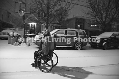 Man in a wheelchair out in a snow storm in a suburban street