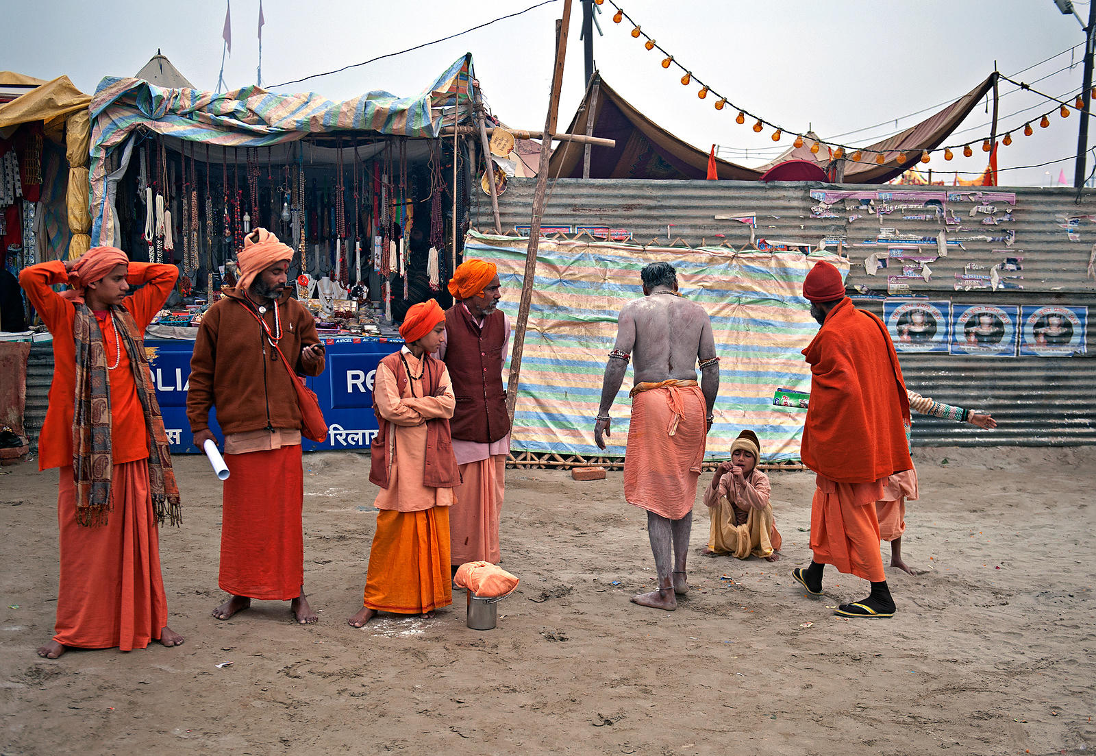 An old saint chats with a boy while others wait for them to finish their conversation. This photograph was shot during the Kumbh Mela.