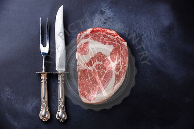Raw fresh marbled meat Steak Rib eye Black Angus and fork and knife on dark background