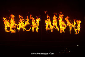 a burning beach party sign with fire flames