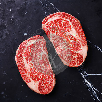 Raw fresh marbled meat Steak Ribeye Black Angus on black marble background