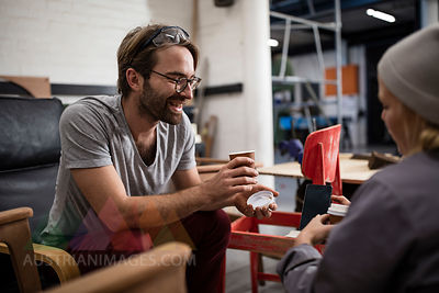 Man and woman drinking coffee in workshop