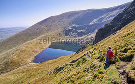 A female hiker walking off the summit of Bowscale Fell with Bowscale Tarn below in the English Lake District, UK.
