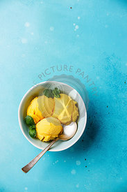 Mango ice cream sorbet with mint leaves on blue background copy space