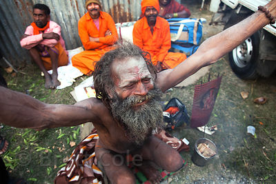 A sadhu (holy man) in Kolkata, India gestures as he prepares to make a pilgrimage to Sagar Island in the Bay of Bengal for the Gangasagar Mela.