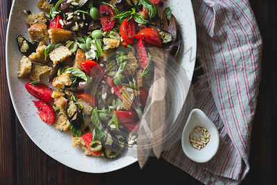Roasted eggplant panzanella with capers, olives, and pine nuts, gluten-free.