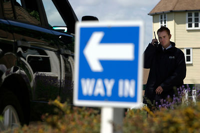 Security Guard examines the licence plate of a vehicle outside The Watermark, A Gated Community, near Cirencester, UK