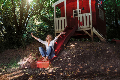 Mature woman sitting on slide in front of garden shed in the woods