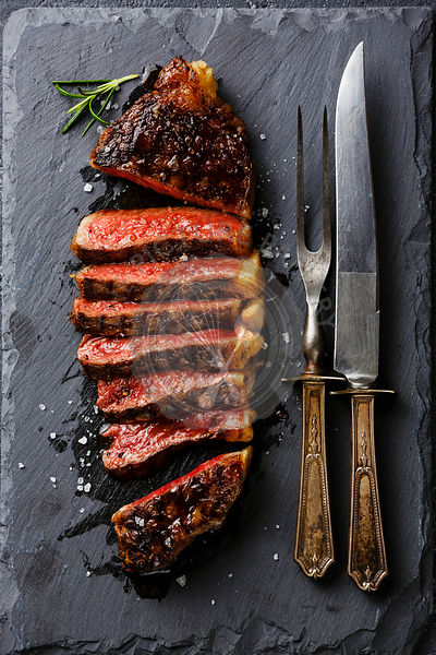 Sliced medium rare grilled Striploin steak with knife and fork on slate board