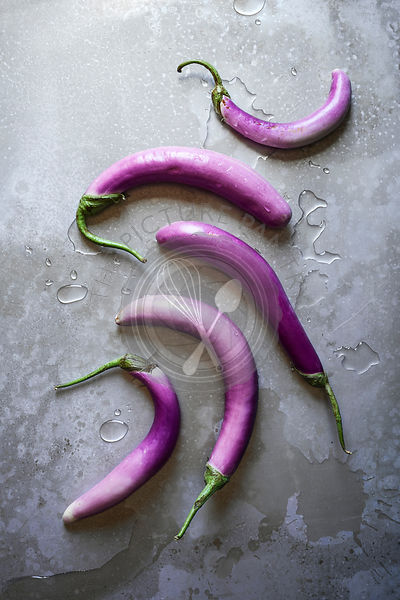 A layout of rich, purple, Asian eggplants with water on a textured wooden surface