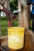 Woman filling bucket with clear water at a hand pump well in the middle of the village in rural Kenya