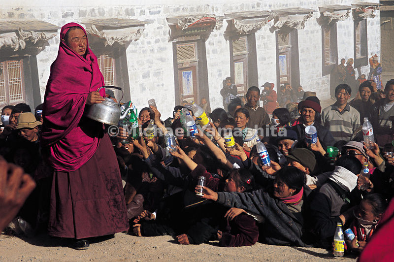 Holding out their bowls, worshippers wait for holy water drawn from the Living Buddha's well. Labrang Monastery, Tibet.