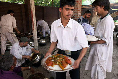 India - Srinagar - A waiter takes tramis (plates) from the Wazas (traditional Kashmiri cooks) to serve to guests at  a Wazwan, a Kashmiri feast