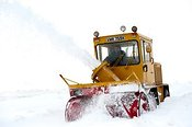 Snow blower clearing a minor road in Cumbria covered in drifting snow