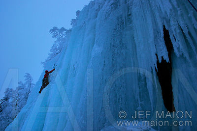 Ice climber and ice stalactites