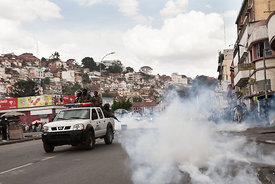 A police car drives by as supporters of ex-president Marc Ravalomanana demonstrated in the center town of Antananarivo on October 18, 2014 after Ravalomanana was placed under house arrest. Madagascar police Saturday used tear gas to break up a rally by supporters of ex-president Marc Ravalomanana, who was placed under house arrest after returning from exile in South Africa. The former president, who was sentenced in absentia to life imprisonment with hard labour, slipped back into Madagascar on October 13, five years after a military coup and two months of violent protests forced him to flee first to Swaziland and then to South Africa.