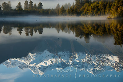 Snow capped mountain peaks (Aoraki / Mount Cook) reflected in a still, fresh water lake with a thin layer of mist framed by green pine trees on the shore.