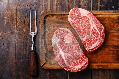 Raw fresh marbled meat Steak Ribeye Black Angus and meat fork on wooden background copy space