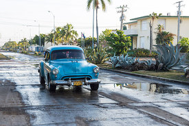 Early morning after a rain storm old cars drive through wet streets in Cienfuegos, Cuba.