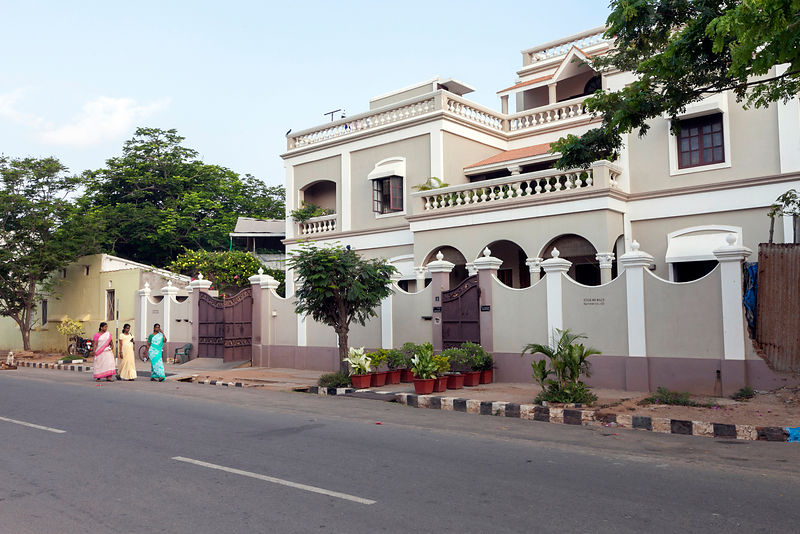 Maids walk to work past a period house, Pondicherry, India