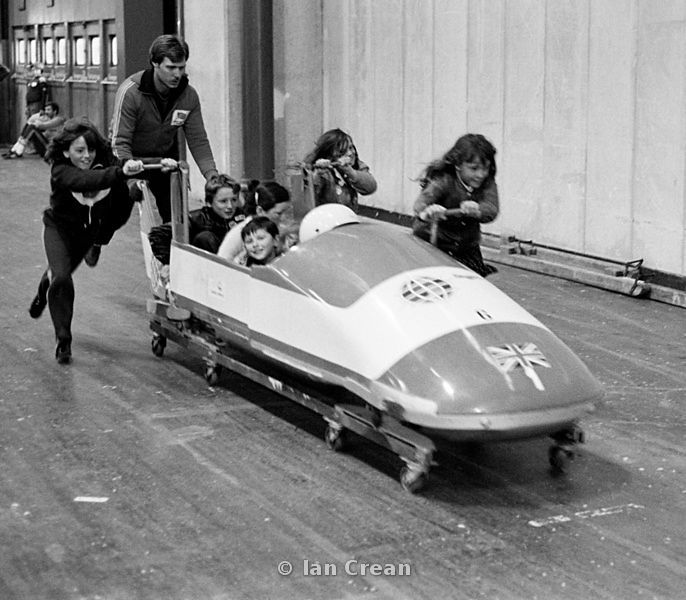 Kids pushing a wheeled bobsleigh