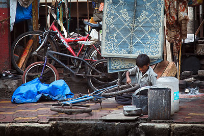 A boy repairs bicycles in a makeshift roadside shop near the Churchgate Railway station in Mumbai, India.