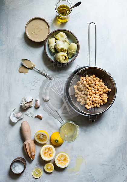 Ingredients for hummus, including chickpeas, garlic, lemon, and artichokes