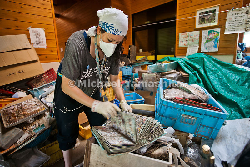 All Hands Volunteers from USA cleaning photo albums found in the wreckage. Pics are cleaned and then photoshopped to restore as much of image as possible then put in new albums for the owners to reclaim. Photorescue@hands.org. Tel 080 3303 4331