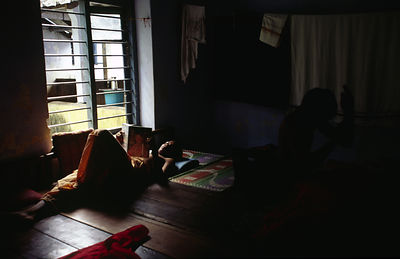 India - Kerala - A student reads whilst another combs his hair in their room