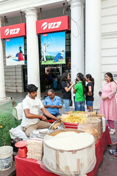 India - New Delhi - A chaat wallah (snack food vendor) makes a dish for waiting customers