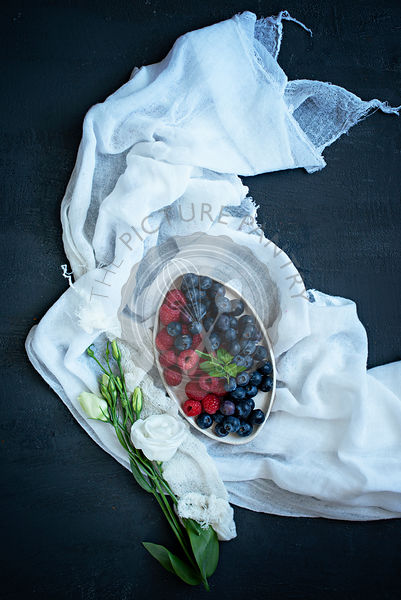 A bowl of summer fruits on white fabric, with flowers.