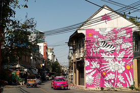 A pink taxi passes by a wall-painted building in Chinatown in Bangkok.