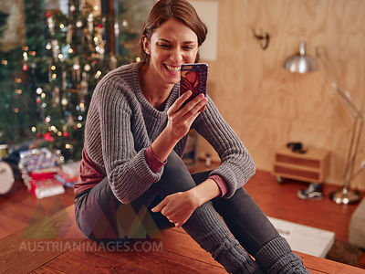Young woman sitting on flooor in front of Christmas tree using smart phone