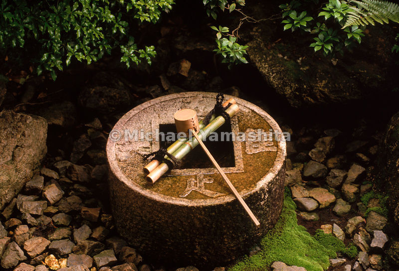 A hishaku, bamboo ladle, sits on an ablution basin inset in a stone in the Ryoanji rock garden in Kyoto. Ritual cleanliness is a key characteristic of Japanese culture.