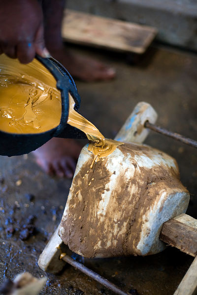 India - Swamimalai - A craftsman pours wax into a mould from which a statue will be cast from bronze