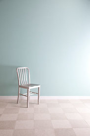 Silver chair next to a light blue wall facing the light.