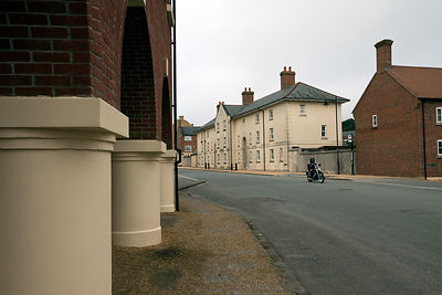 UK - Dorset - A man rides his motorbike past traditionally styled buildings Poundbury.