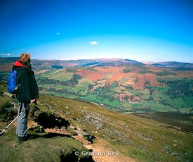 walker looking at view of the black mountains from the summit of sugarloaf mountain abergavenny south wales