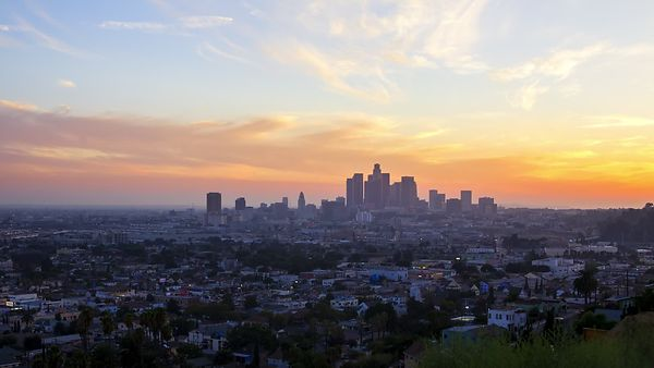 Wide Shot: Burning Sun Rays Receding Over Altostratus Clouds & A Lit Skyline Of Neighborhoods Amongst High-Rises