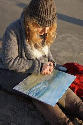 Artist painting with soft oil crayons at the beach Evening light