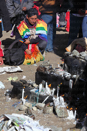Pilgrim praying at foot of cross on trail during Qoyllur Riti festival, Peru