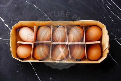 Guinea-fowl eggs in eco tray container on marble background